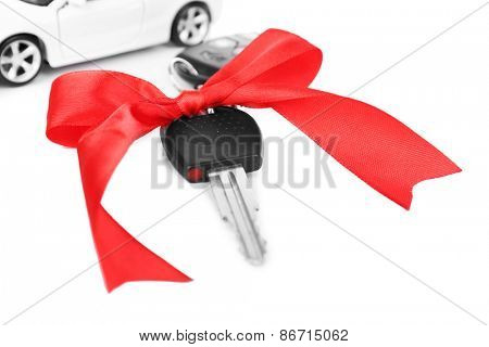 Keys with red bow and car as present isolated on white