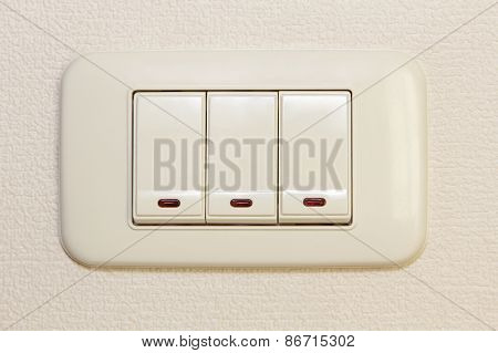 Threefold Multiply Light Switch On Beige Wall.
