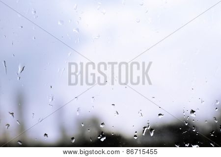 Raindrops on glass window overlooking the street on background
