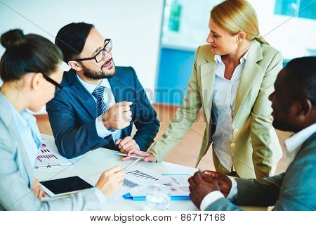 Happy businessman talking to pretty employee at meeting with colleagues near by