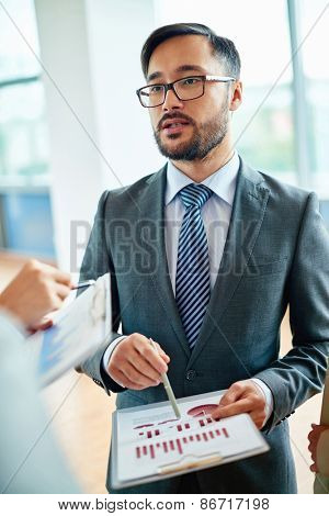 Elegant businessman explaining data to colleagues at meeting