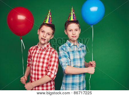 Cute twins with balloons looking at camera