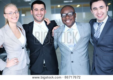 Cheerful business partners in suits looking at camera