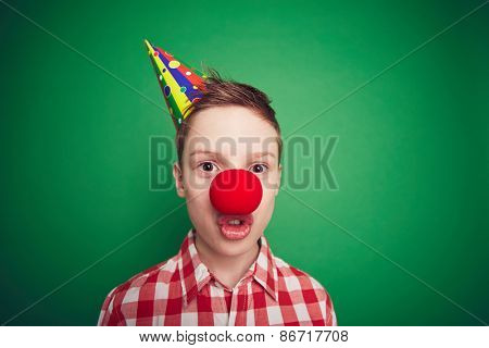 Cute boy with red clown nose grimacing