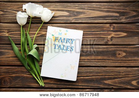 Fairy Tales book with white tulips on wooden background