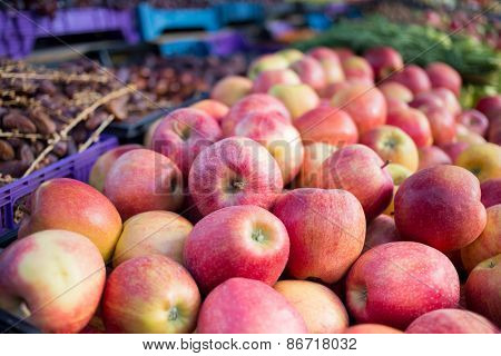 Fresh red apples and vegetables in an outdoor market