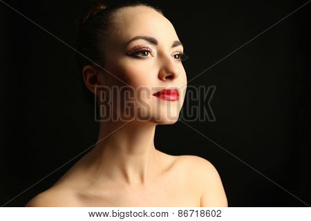 Portrait of beautiful woman with fancy glitter makeup on dark background
