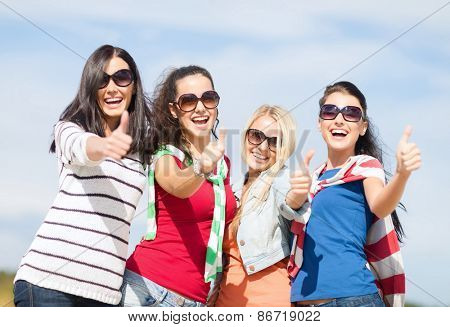 summer holidays, vacation and people concept - happy teenage girls in sunglasses or young women showing thumbs up on beach