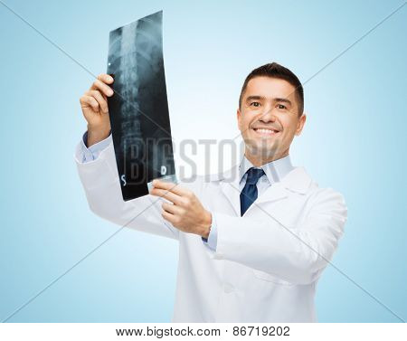 healthcare, rontgen, people and medicine concept - smiling male doctor in white coat with x-ray over blue background