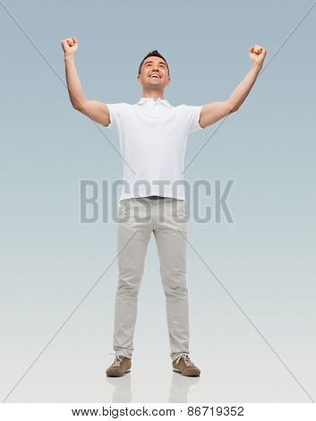 happiness, gesture and people concept - happy man with raised hands over gray background
