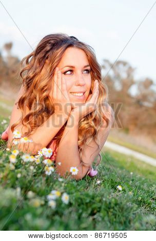 Pretty cool woman lying on the grass surrounded by flowers