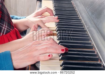 Hands of two people playing the piano. Closeup women and little girl hands