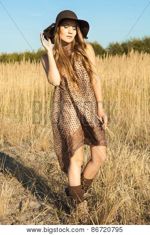 Beautiful Young Lady Model Wandering Through Meadow At Midday