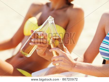 summer holidays and vacation - two girls in bikinis with drinks on the beach chairs