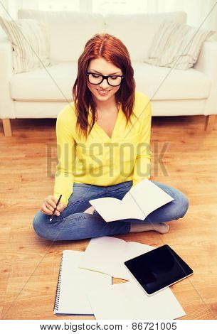 home, education, technology and people concept - smiling teenage girl sitting on the floor with tablet pc computer and workbook at home