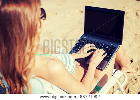 summer holidays, vacation, technology and internet - girl looking at laptop on the beach chair