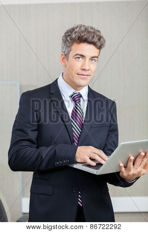 Portrait of confident businessman with laptop at call center