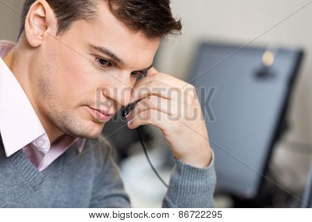 Closeup of serious male customer service representative in office