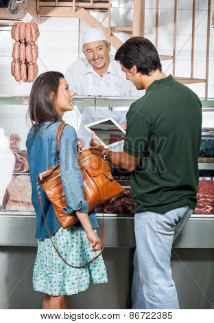 Mature couple using digital tablet while standing at counter of butcher shop