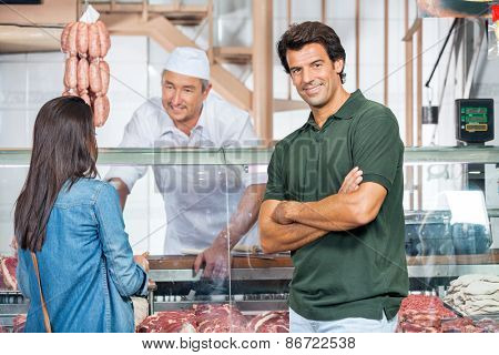 Portrait of happy mature man with woman buying meat at butchery