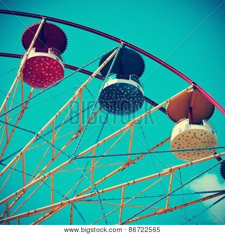 closeup of a colorful vintage Ferris wheel over the blue sky, with a retro effect