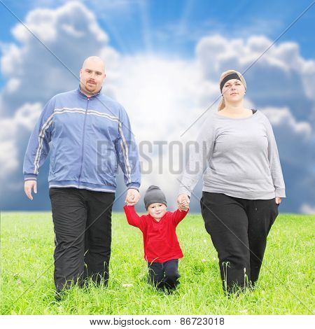 Overweight parents with her son  playing together on spring meadows.