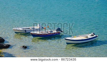 Row of three moored boats at the sea shore