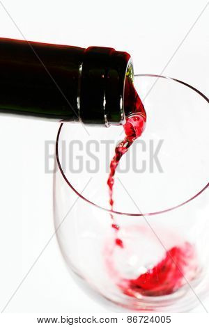 Red wine pouring into glass isolated on white background