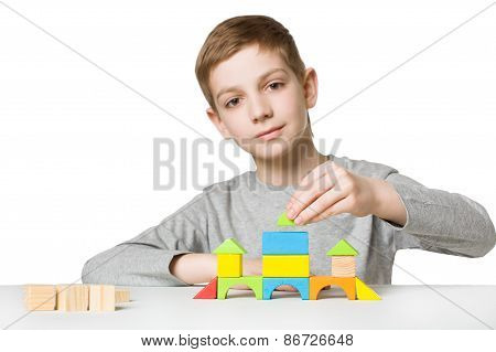 Portrait Of A Boy Building House Of Wooden Blocks