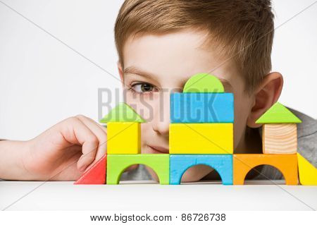 Portrait Of A Boy Hiding Behind House Made Of Wooden Blocks