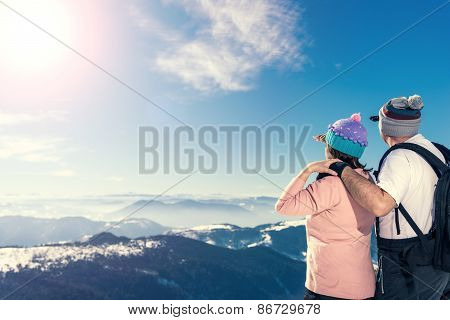 Middle Aged Couple Looking Away On The Top Of The Mountain