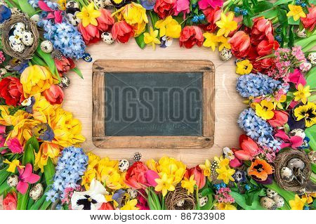 Holidays Background With Chalkboard. Spring Flowers And Easter Eggs