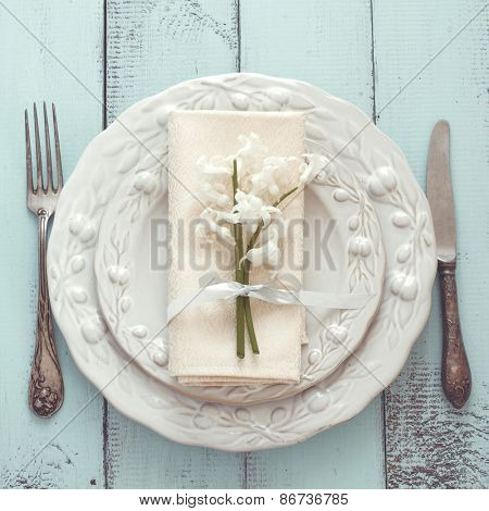 Spring shabby chic table setting on mint wooden background, top view point