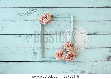 Wooden photo frame with lace and flowers on mint shabby chic background