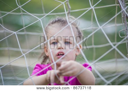 Little girl behind football net
