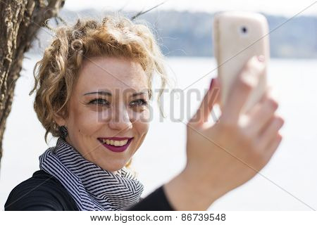 Young Curly Blond Woman Taking Picture Of Herself