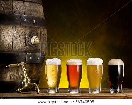 Still life: old wooden pin of beer, glass of beer and wheat on the table in the cellar.