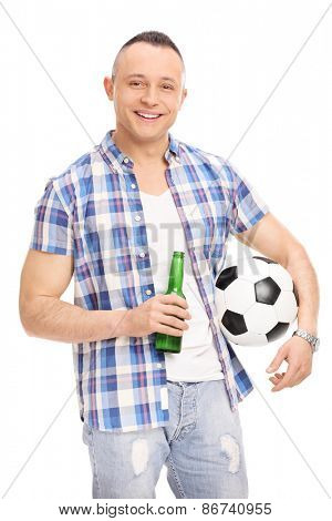 Vertical shot of a cheerful young guy holding a bottle of beer and a football isolated on white background