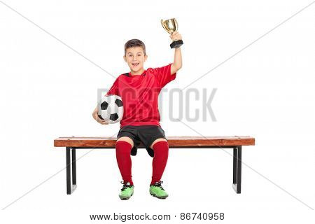 Delighted boy in soccer uniform holding a trophy in one hand and a ball in the other, seated on a bench isolated on white background