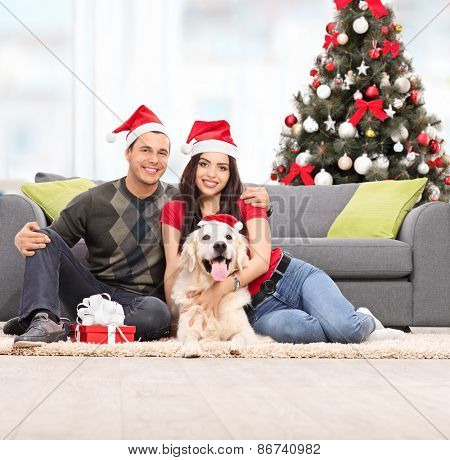 Young couple celebrating Christmas with their dog seated on the floor next to a modern gray sofa at their home