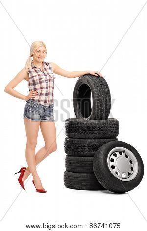 Full length portrait of an attractive female worker in a checkered shirt and glossy red high heels standing next to a stack of tires isolated on white background