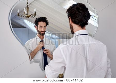 professional man getting ready morning routine shirt and tie in bathroom at home