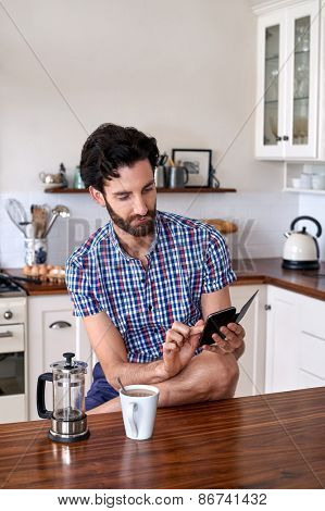 man enjoying french press filter coffee with mobile cellphone at home kitchen