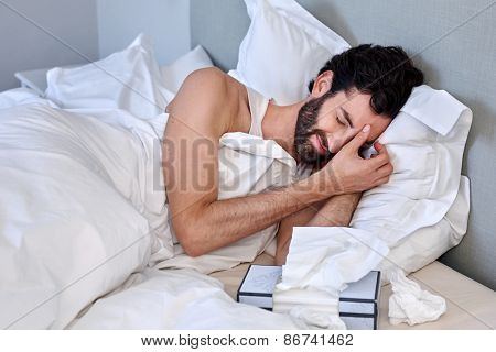 depressed sad sick man with tissues in bed at home