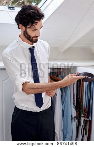 professional man getting ready for work choosing belt from bedroom cupboard