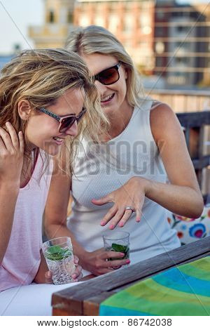 attractive young woman showing friend her engagement ring outdoor on the rooftop terrace