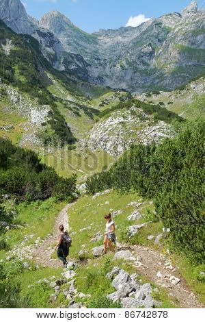two young female go down a path in a valley of Durmitor National Park, Montenegro