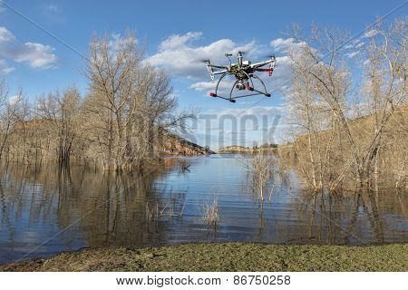 FORT COLLINS, CO, USA, March 30,  2015:  DJI F550 Flame Wheel  hexacopter drone is  flying with a camera in early spring over  lake.with submerged cottonwood trees.