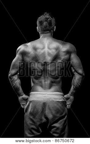 Muscular male model bodybuilder preparing for fitness training, turned back