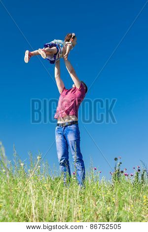 Outdoor Portrait Of A Father Who Throws Daughter In The Air Against The Sky